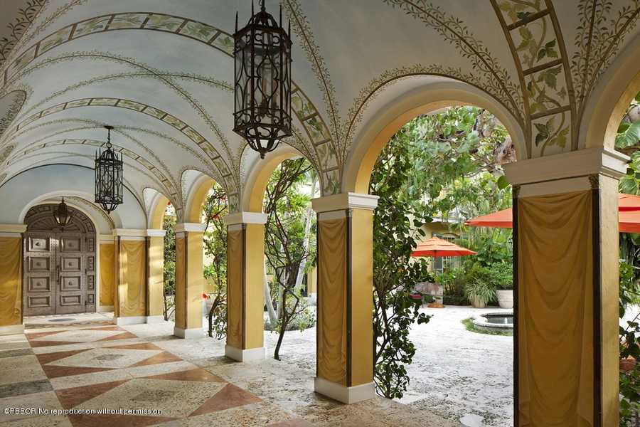 Arches, columns, beautifully designed marble tiled floors, and ceiling murals before you even enter this mansion.