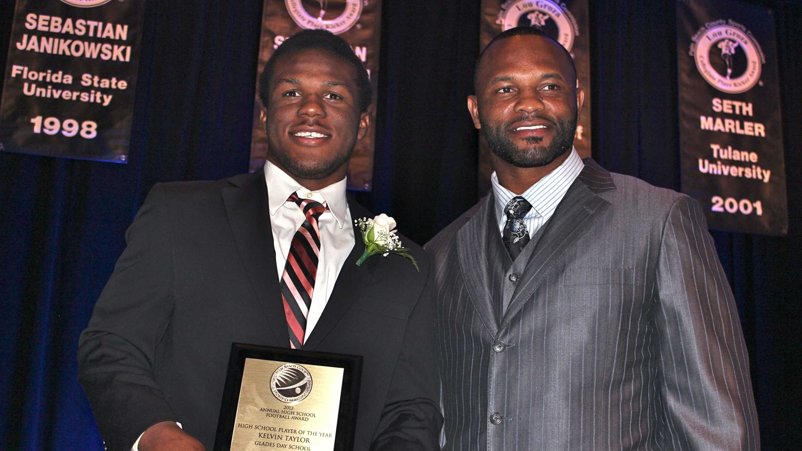 Glades Day School senior running back Kelvin Taylor poses with his father, Fred Taylor, after being awarded the 2012 Palm Beach County high school player of the year. Fred Taylor won the same award in 1993.