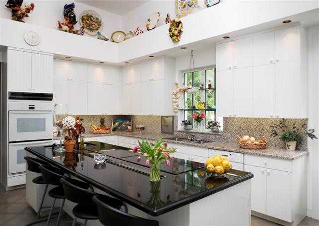 This kitchen features an island with a built in stove and dining bar.