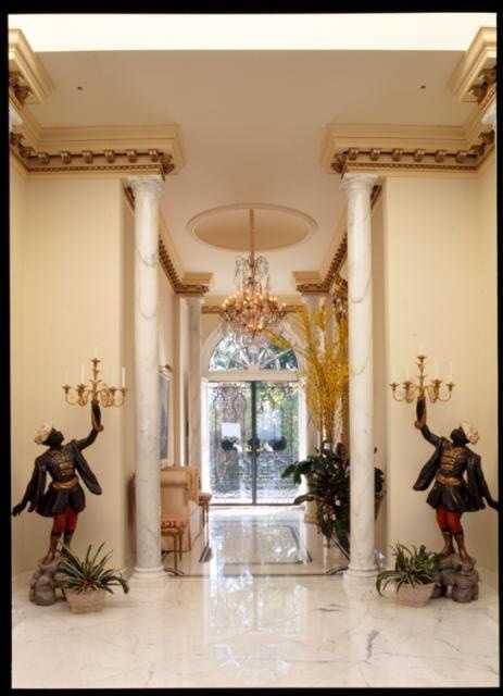 Grand entrance way gives the impression of opulence with the chandelier, marble columns, and candelabras on either side.