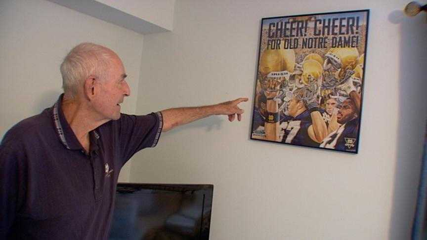 Ray Burtka points to a Notre Dame poster at his home. He has followed the Fighting Irish for most of his life.