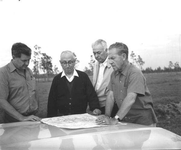 Roy Disney and others survey a map.