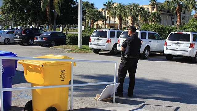 A police officer guards the suspicious package that was delivered to the WPBF 25 News studios on Monday.