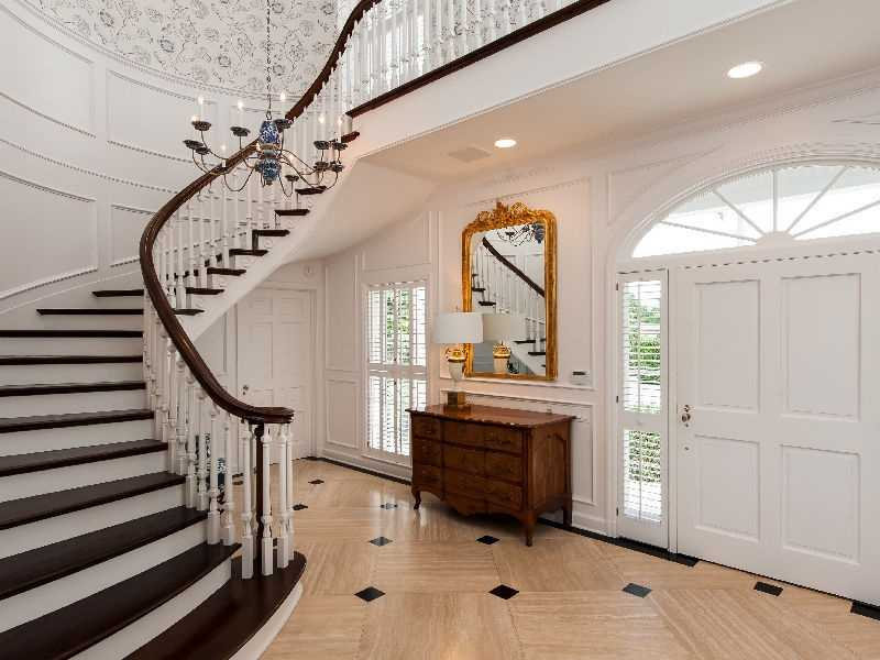 Bright white foyer and winding staircase.