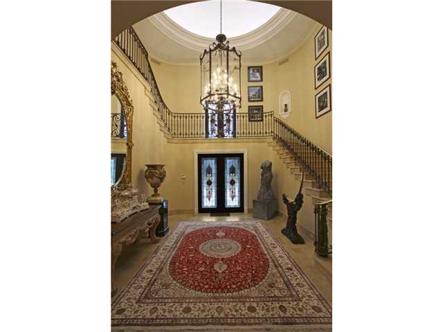 The foyer of this two-story home features classic, antique pieces and beautiful, vaulted ceilings.