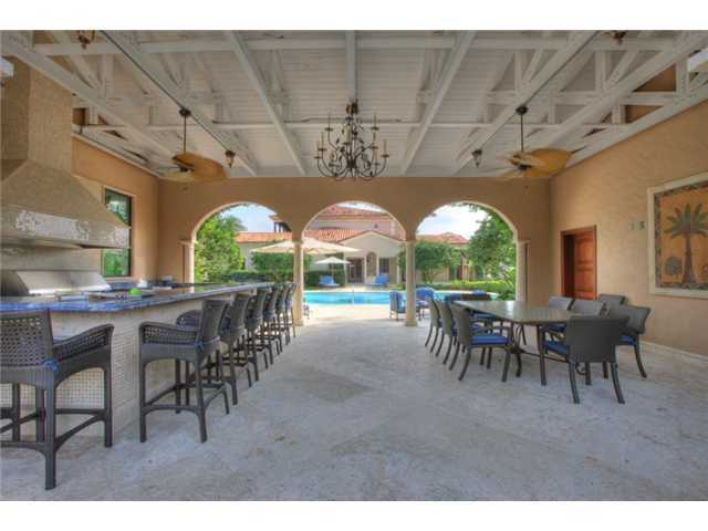 Expansive outdoor bar, grill, and sitting area by the pool. Perfect for entertaining and large outdoor parties.