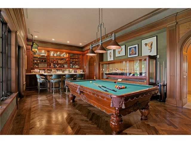 Chic billiard is complete with a custom-wooden wet bar.