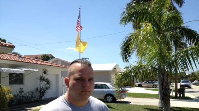 U.S. Marine veteran Gregory Schaffer proudly stands in front of the flagpole in his front yard.