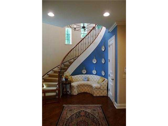 Winding staircase nestles a sitting area.