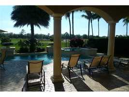 Covered patio offers shade as you look out over the pool and golf course.