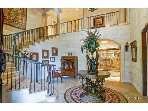 The foyer features a cascading marble staircase that reach a pillared entrance on the second floor.