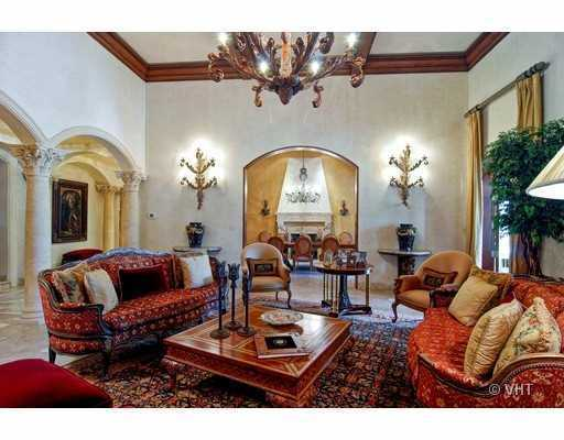 Formal living room features an antique elegance, wooden trimming along the ceilings and marble floors.