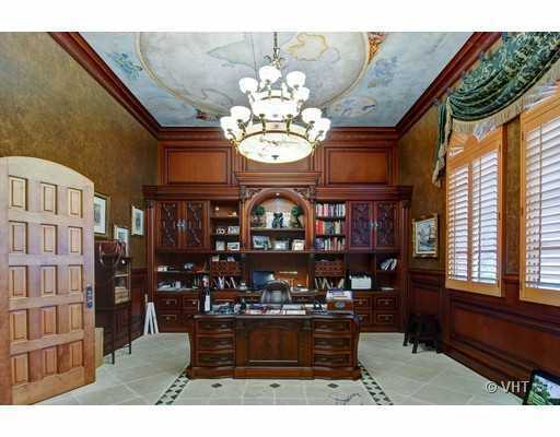 This office features a ceiling mural and custom wooden unit and desk.