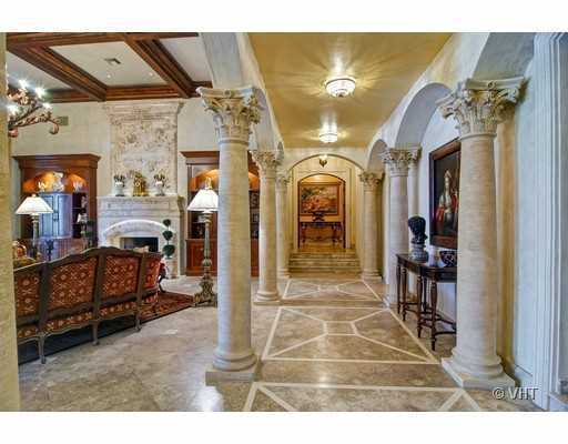 The hallways feature a custom tile pattern. Roman columns are featured throughout the home.
