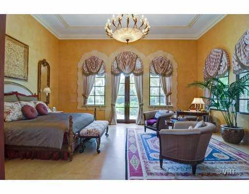 Master bedroom is features a balcony and beautiful windows.