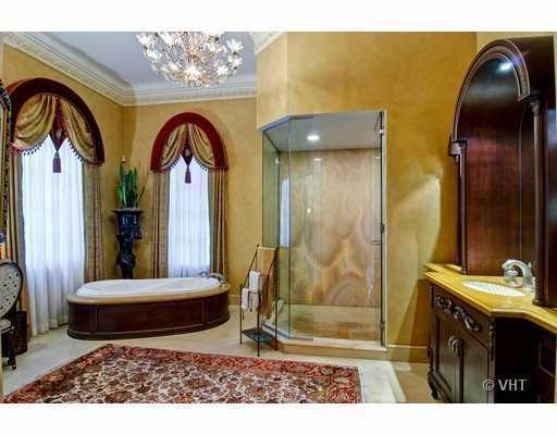 Master bathroom features a custom spa tub, a spacious shower, and vanity set.