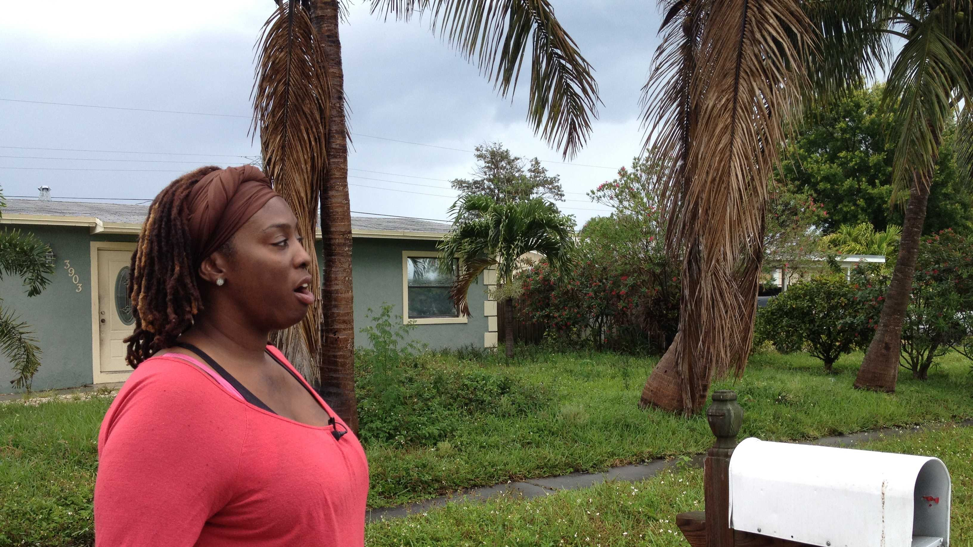 Naomie Breton, who was set on fire by her ex-fiancé last year, stands outside the Lantana home that squatters have taken over, but authorities can't do anything about it.