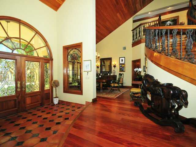 Gorgeous custom hardwood lines the floors and the ceilings of the foyer.