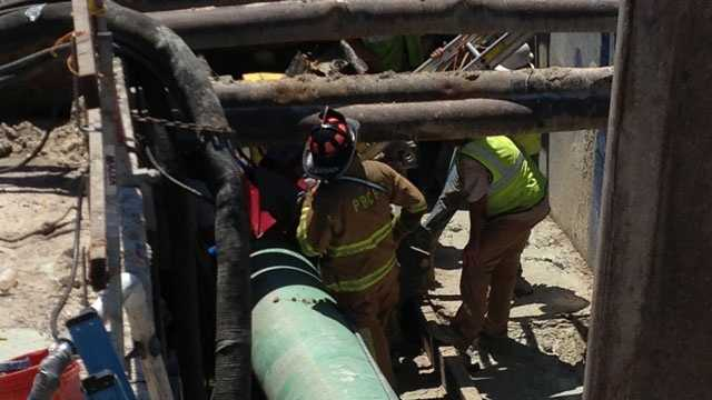 Rescuers help a worker who was injured at a construction site near Seminole Pratt Whitney Road and Beeline Highway.