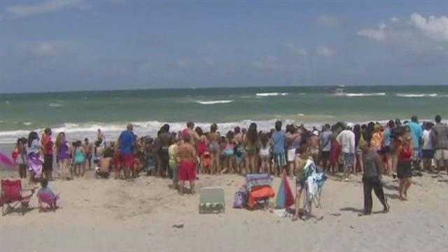 Beachgoers try to help a teenager who was swept under the water by a wave at John U. Lloyd Beach State Park.