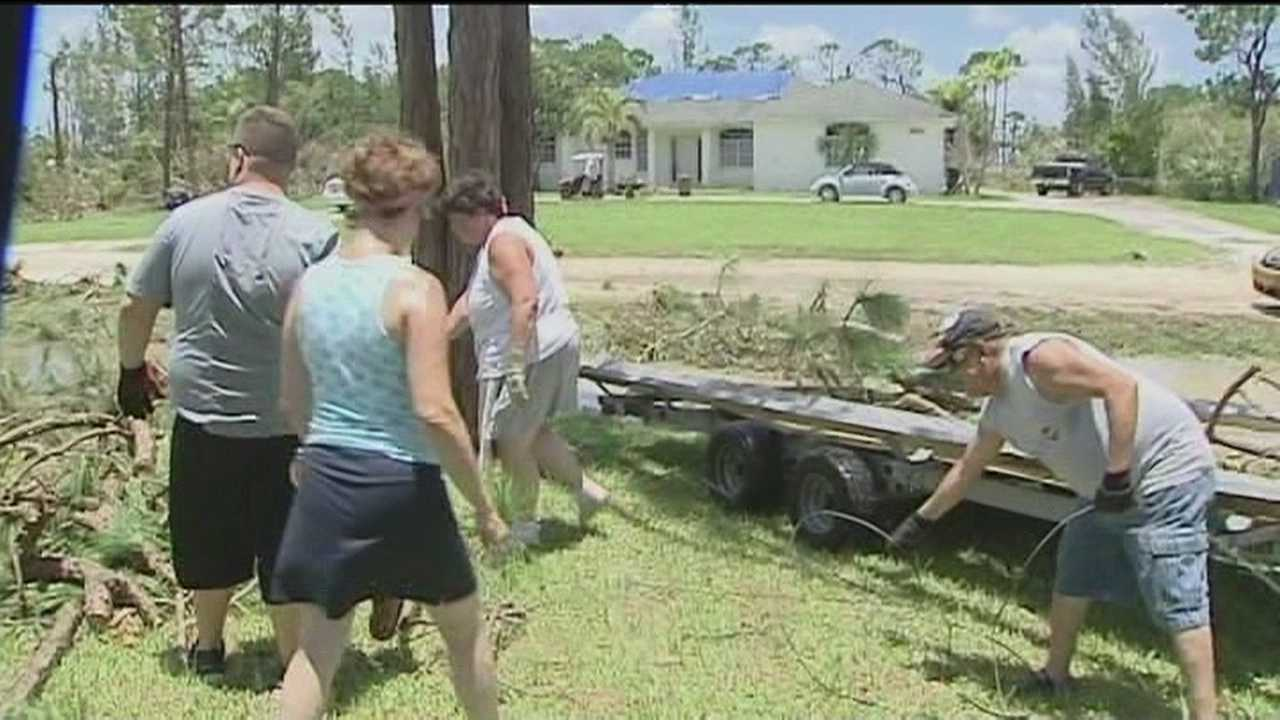 Neighbors, strangers and co-workers help cleanup debris after Thursday's tornado in Loxahatchee.