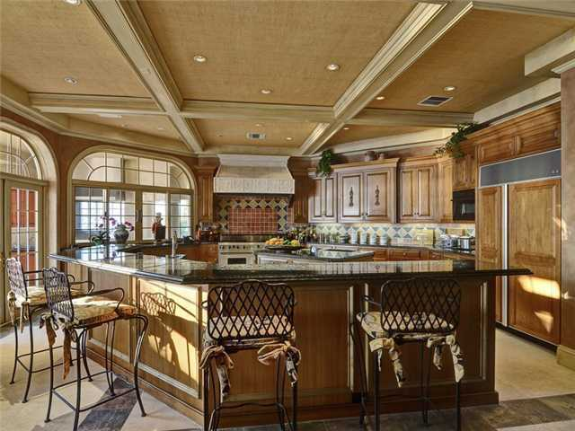 This dream kitchen features a chef's preparation area, custom cabinetry, dining bar, and state of the art tools.