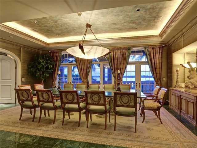 What you might first notice about this dining room is the The dining room, which seats twelve, features green marble floor and a contemporary chandelier.