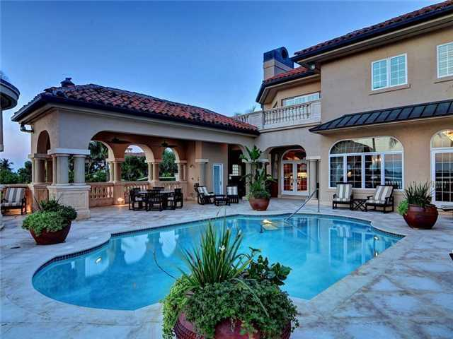 The pool area looks like an elegant resort! This view showcase the architectural design of the back of the home, canopy, and shaded areas.