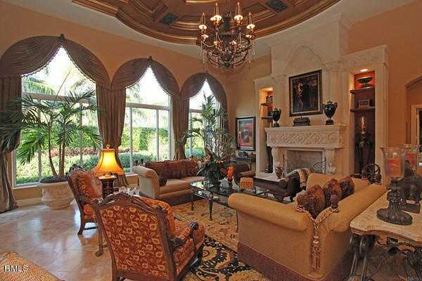 Formal living room features floor-to-ceiling expansive arch windows and custom marble fireplace.