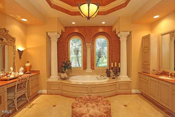 Master bathroom features Roman columns and a large spa tub.