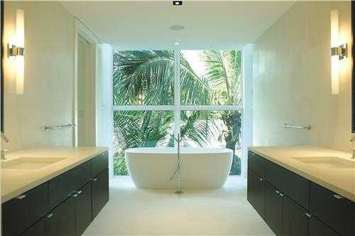 The master bathroom features a serene spa-like bath with Agape tub, Philippe Starck fixtures, Kohler glass-enclosed shower, and Waterworks lighting.