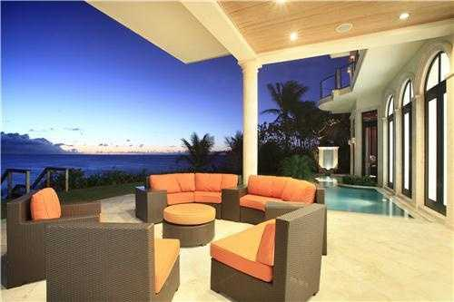 Breathtaking oceanfront pool next to a covered patio area.