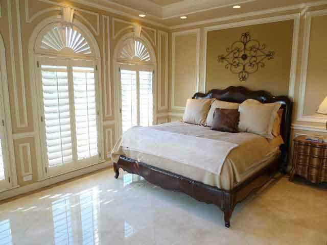 One of five bedrooms, features arched windows and marble floors.