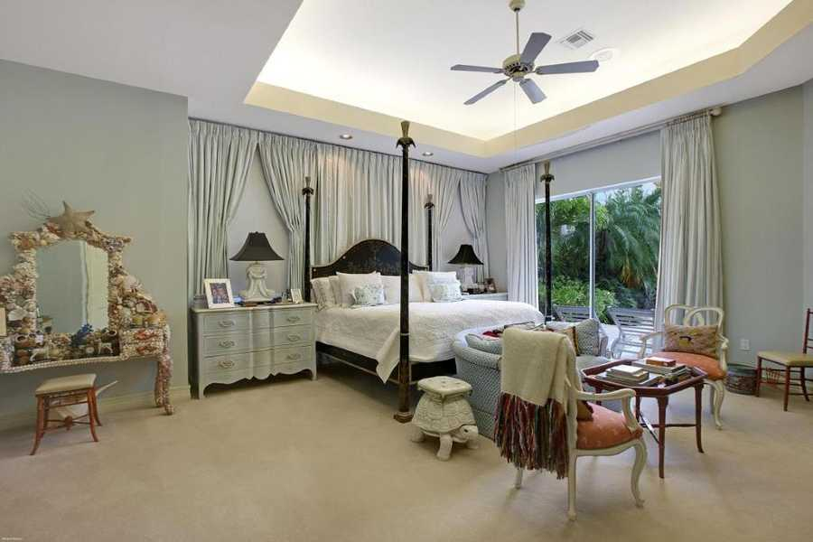 Romantic master bedroom looks out over the patio.