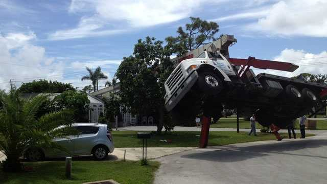 This crane was being used to replace an air-conditioning unit when it toppled over and landed on a house.