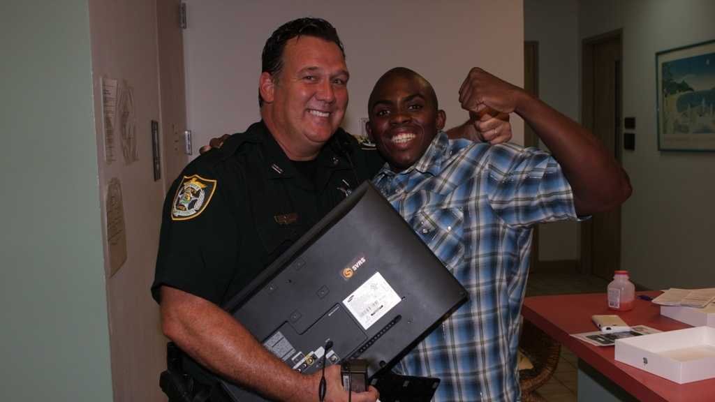 Deputy Greg Farless poses with Carl Johnson and his TV.