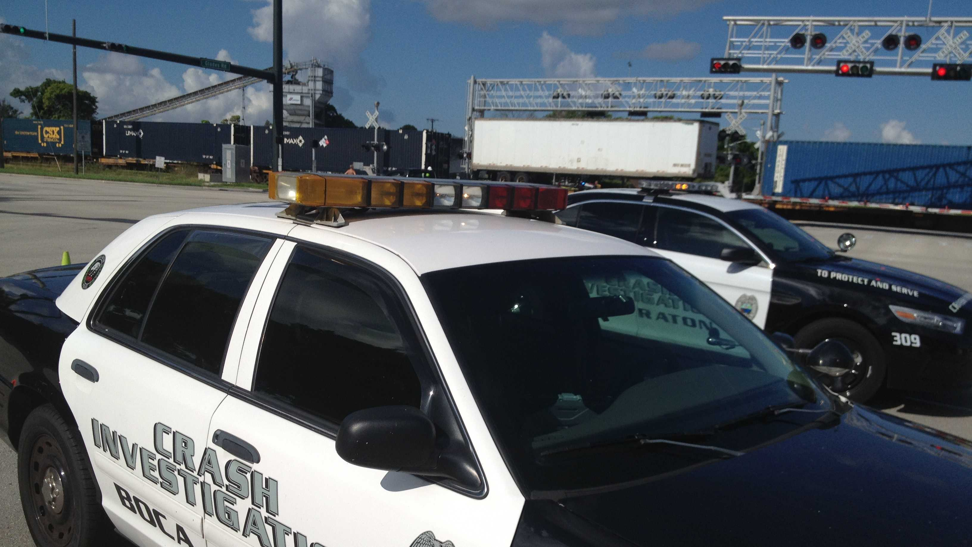 A CSX train blocks the intersection of Dixie Highway and Glades Road in Boca Raton after a fatal crash.