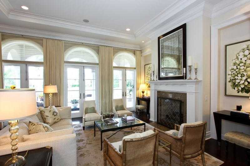 The focal point of this formal white living room is the custom fireplace.