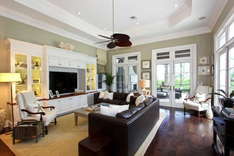 Comfy family room features a custom, modern entertainment unit and access to the patio.