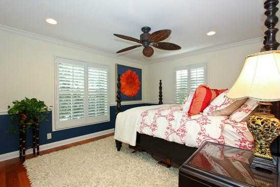 The final bedroom features more windows and a pop of blue color on the walls.