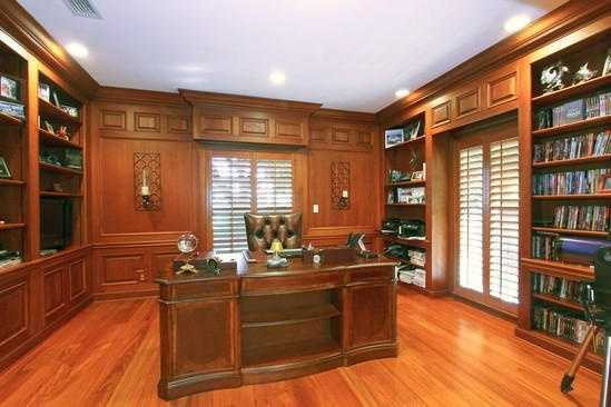 Dreamy office with cherry wood shelving and desk.
