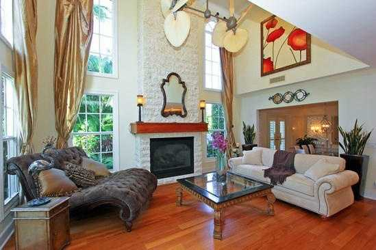 The formal living room features soaring ceilings, floor-to-ceiling windows and a fire place.