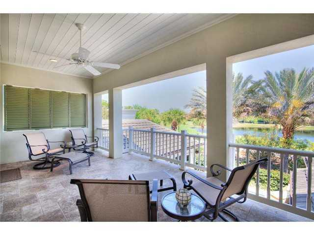 Generous balcony looks out over the golf course, lake, and pool.
