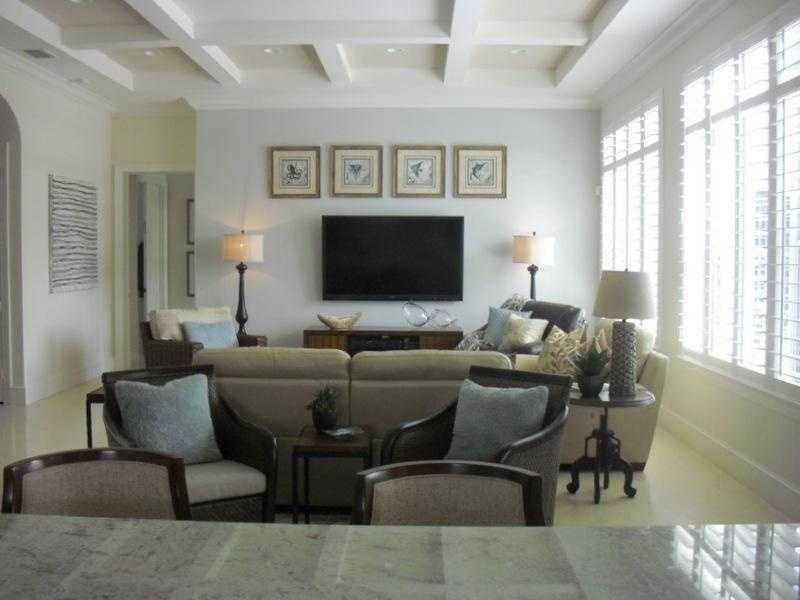 The living room features dramatic wooden beamed ceilings and large floor to ceiling windows.