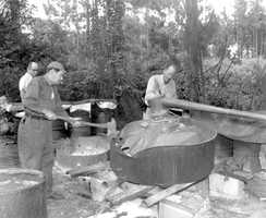 1953: A moonshine still being broke apart.