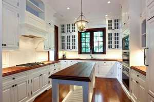 Custom cabinetry surrounds the large gas stove.