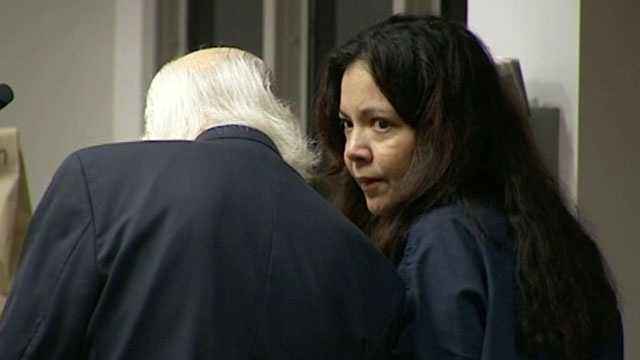 Annybelkis Terrero listens to her attorney in court. She is accused of asking two police officers to help her hire a hit man to kill her husband.