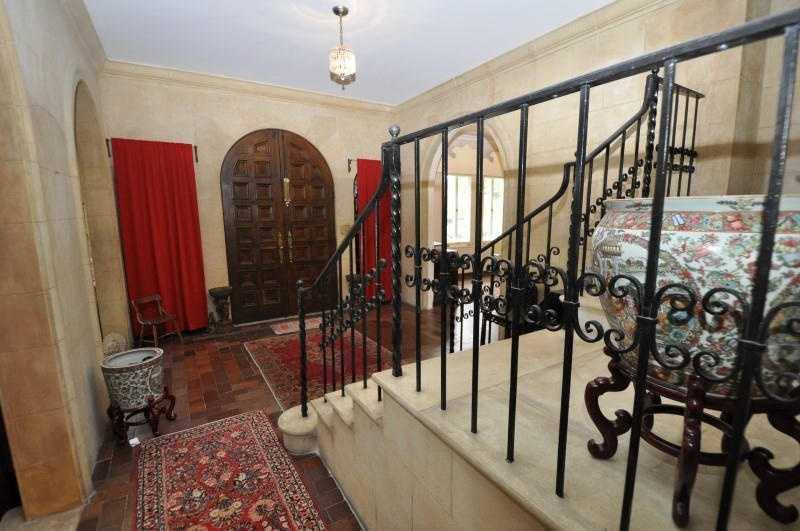 The entry foyer is stunning with stone block walls, quarry tile floors, radius top wooden double entry door, radius top stone cased openings and wrought iron four landing stairway.