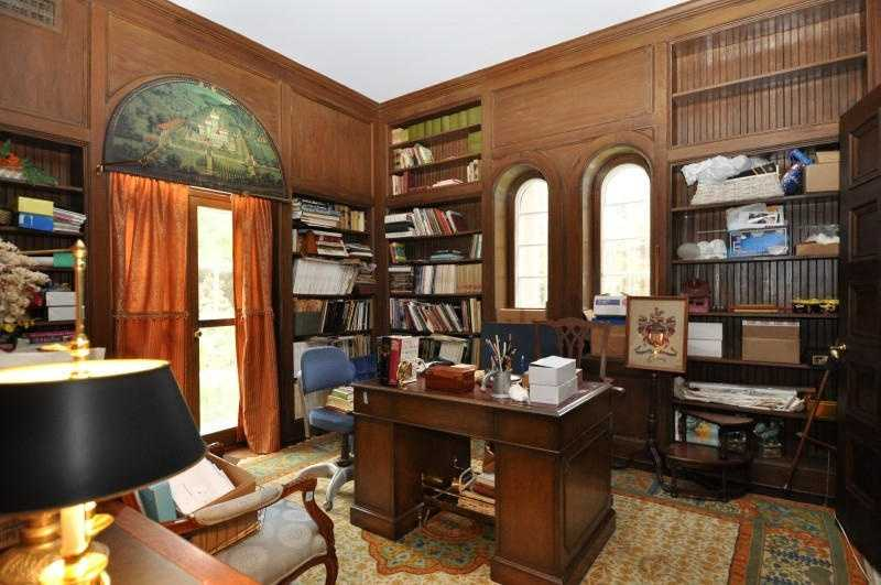 A wood paneled library is tucked behind a marvelous step down powder room.