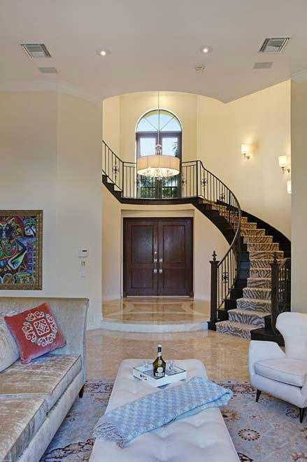 Alternate view from the living room shows the grand, winding staircase above the front door.